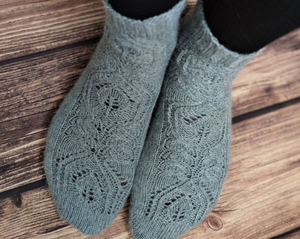 Hedera socks by Coraline in the Fibre Co. Amble. Woman wearing pair of grey lace socks.
