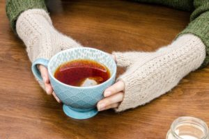 Hands cupping a blue teacup, wearing a pair of beige cabled mitts.