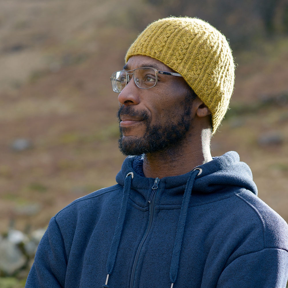 A man looking away from the camera is standing on the fells in Cumbria wearing a hand knitted mock cable beanie hat and hoodie| Gifts you can make.