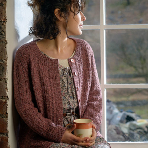 Woman sitting in a window seat with a cup of tea wearing a hand knit cardigan.   Hodgsons Joy by Sarah Hatton knitted in The Fibre Co. Lore