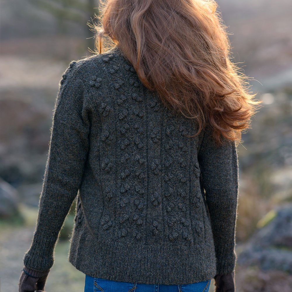 Woman is photographed from behind walking in the fells. She is wearing a cardigan with decorative bobble stitch pattern.
