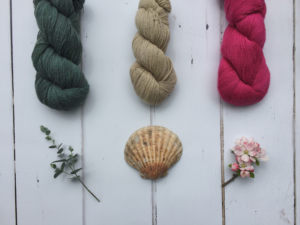 Natural fibre yarns in pretty colours with plants and a shell