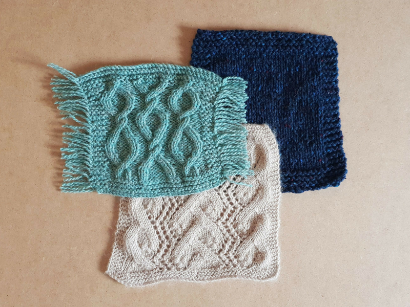 Three handknitted swatches in stockinette, cable and lace.