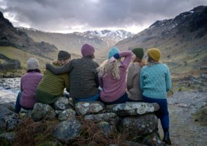 Six women wearing knitwear sat on a rock