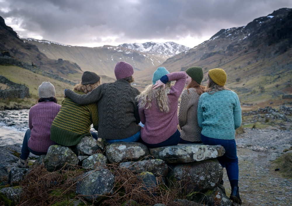 Six women wearing knitwear sat on a rock