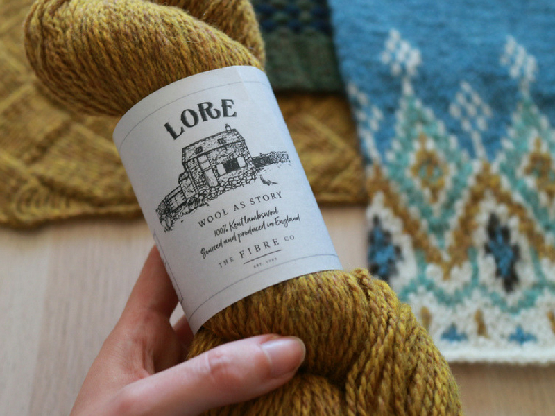 The Fibre Co. Lore in Happiness against background of knitted swatches