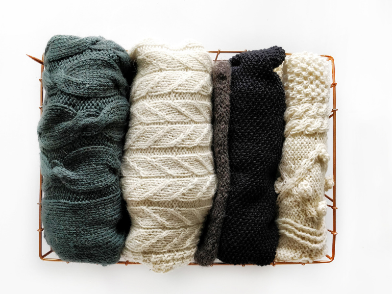 Basket of hand-knitted sweaters including Brandelhow in The Fibre Co. Lore in Logical