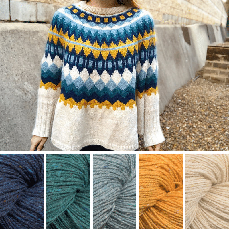 Woman wearing colourwork sweater in dark blue, teal, pale blue, yellow and cream