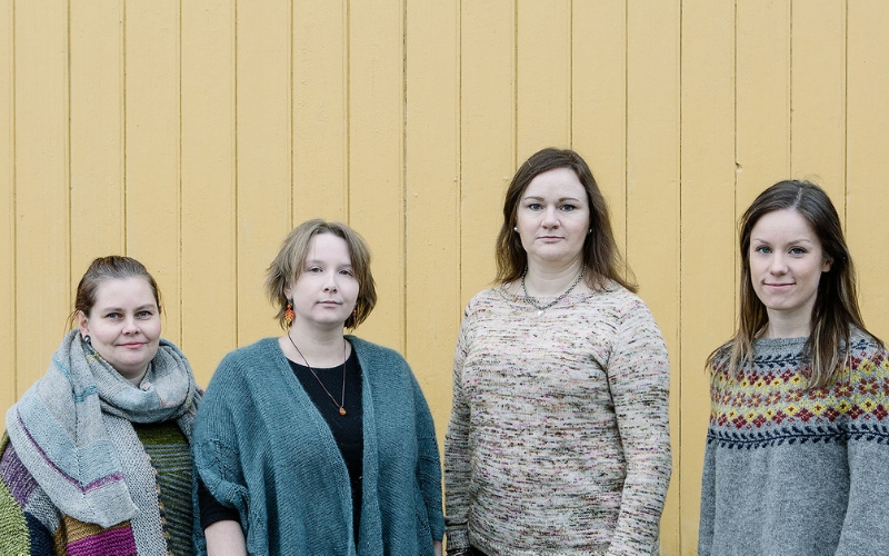 Four women wearing handknit sweaters stand against a yellow wooden wall