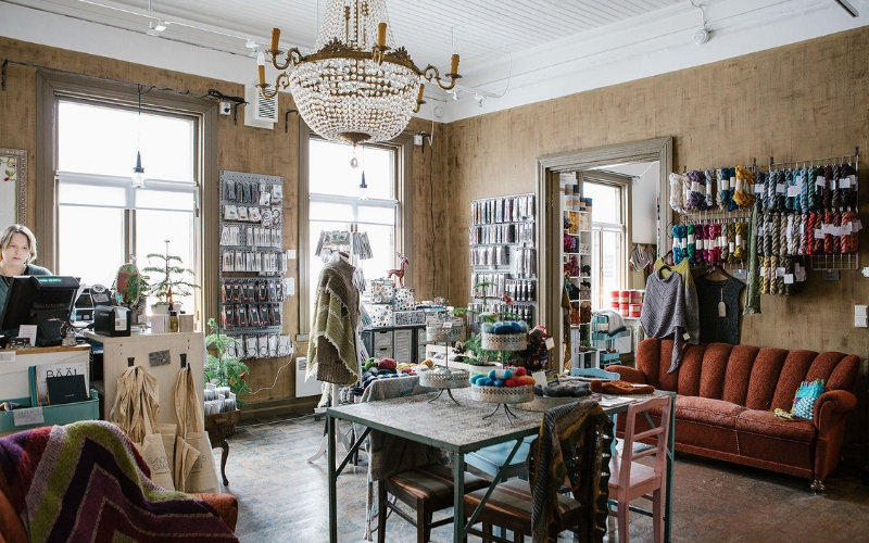 Photo of TitiTyy yarn shop. Its a bright, warm looking shop with rustic furniture, a plush sofa and a large chandelier in the centre of the room. There is beautiful yarn in every colour all over the room.