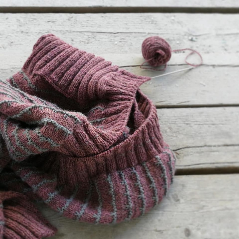 A pink and lilac knitting project in progress is placed casually on a wooden slatted table. It's hard to see what it is yet, but it has beautiful slipped stitch colourwork and deep ribbing. A small ball of yarn is placed next to it.