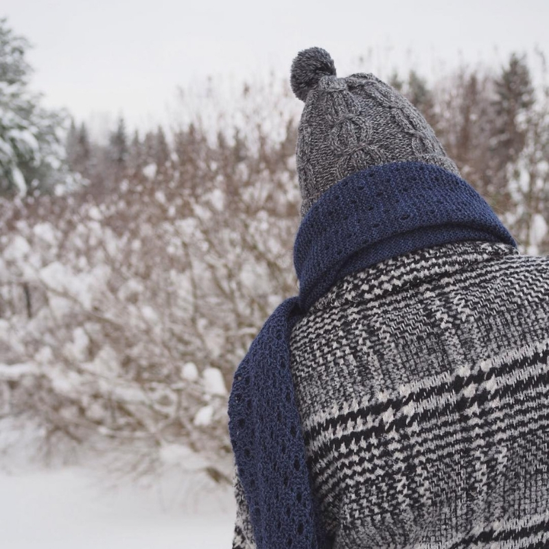 On a snowy day, a figure has their back to us, looking towards trees covered in snow. They are wearing a blue textural shawl with a grey cabled hat and a grey checked coat.