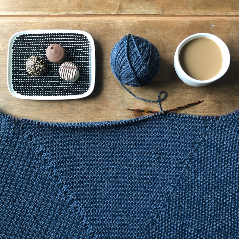 A blue knitting project in progress is placed on the table with wooden needles still attached. The ball of yarn is above it, alongside a hot cup of tea and a geometric plate with three chocolate truffles on it.