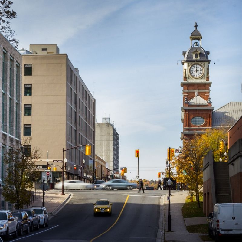 A street in Peterborough Ontario. The sun is shining and there is a clock tower in the distance. Cars pass by at the crossing.