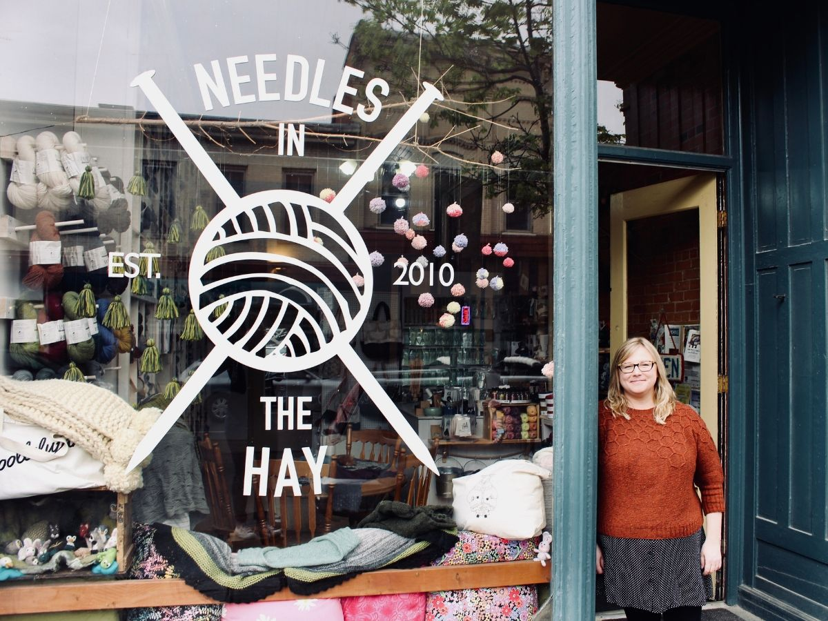 Owner, Deanna Guttman, stands in the doorway of her yarn shop, Needles in the Hay