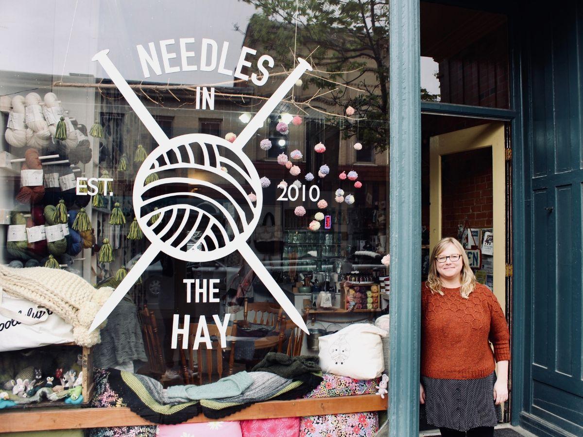 Owner, Deanna Guttman, stands in the doorway of her yarn shop, Needles in the Hay