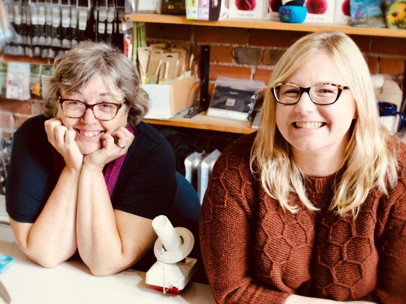 Deanna and her colleague sit at a table in her yarn shop and smile at the camera