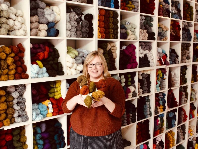 Deanna is holding a bundle of yarn and stands in front of a giant wall of yarn in her shop, smiling.