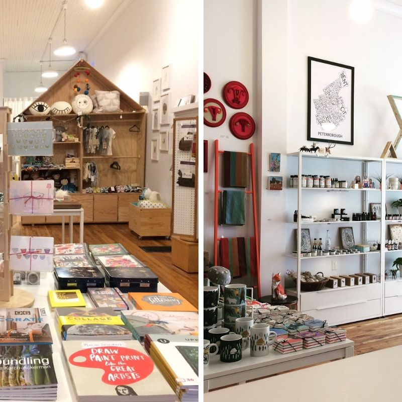 1. Books and cards are displayed on a table. In the background is a shelving unit in the shape of a house with handmade goods on display. 2. Mugs and coasters are place on a side table. On the wall is displayed local art and on shelves, you can see ceramics and little bottles.