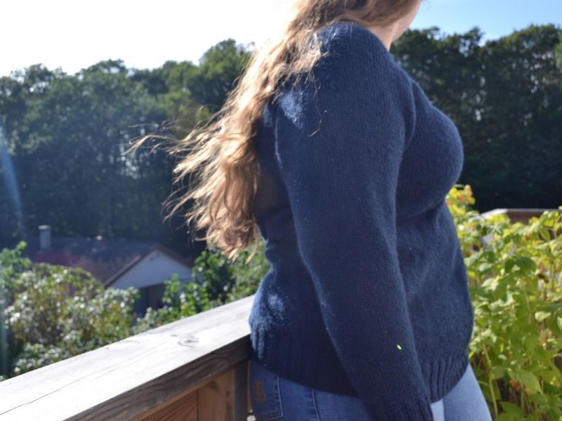 Anine is wearing a navy blue sweater and wearing their hair long and wavy. They are leaning against a balcony with lots of trees in the background   Introducing One Sweater: a Wardrobe Classic in Cumbria
