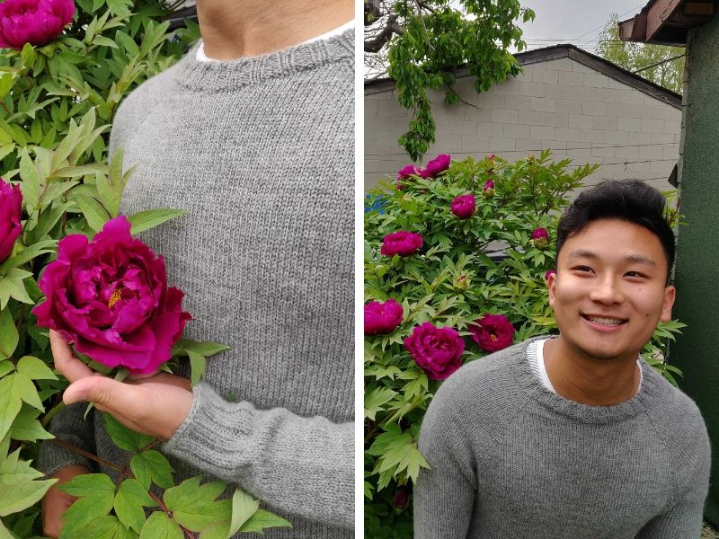 Darren's brother is wearing a One Sweater in pale grey. He is standing next a hedge with large pink flowers on them which contrast beautifully against his neutral sweater. | Introducing One Sweater: a Wardrobe Classic in Cumbria