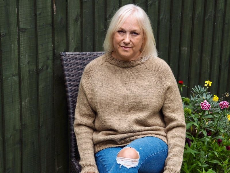Deb is sitting in her garden wearing a camel One Sweater. It has a relaxed fit and looks fantastic with the ripped jeans she is wearing. | Introducing One Sweater: a Wardrobe Classic in Cumbria