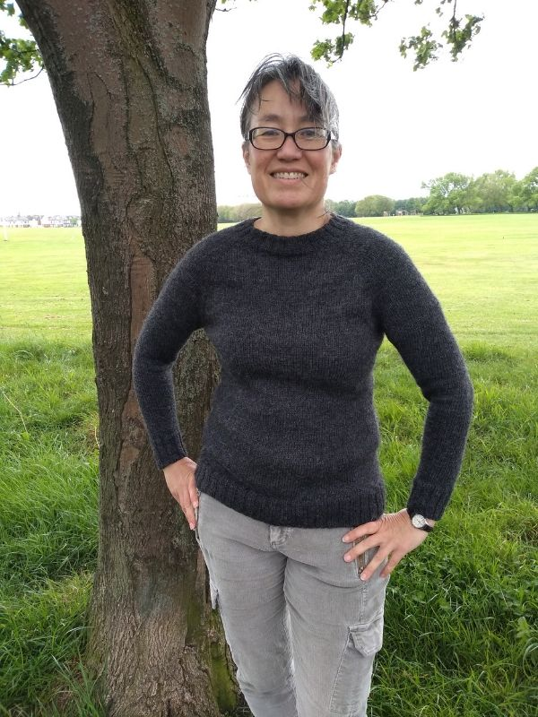 Maylin is wearing a dark grey One Sweater with a neat, close fit. She is smiling in front of a tree and large field. | Introducing One Sweater: a Wardrobe Classic in Cumbria