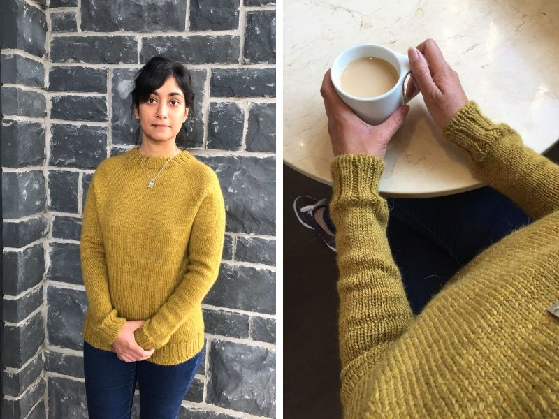 Nidhi is wearing a golden yellow One Sweater and standing against a grey brick wall. In the next picture, she is holding a cup of tea in her hands. You can see the neat cuff detailing. | Introducing One Sweater: a Wardrobe Classic in Cumbria