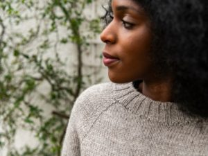 Close up of Joy, our model, wearing a One Sweater in an oatmeal colour. She is gazing to the side with lots of vines behind her.