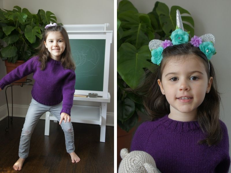 Samantha's daughter is wearing a rich purple sweater with grey trousers. She is playing in front of a chalkboard. In the second picture, she is wearing a sweet unicorn headband and holding a stuffed toy. | Introducing One Sweater: a Wardrobe Classic in Cumbria