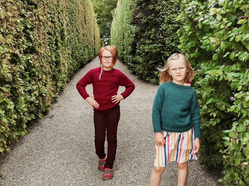Solveig's daughter are both wearing One Sweaters - one in turquoise and one in red. They are both posing in a way that almost makes them look like a girl band! | Introducing One Sweater: a Wardrobe Classic in Cumbria