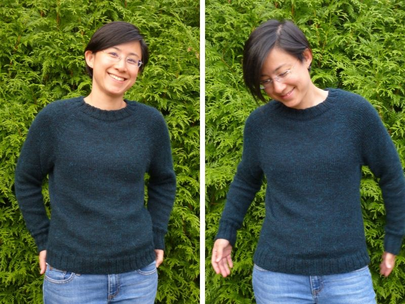 Alexandra is wearing a deep teal One Sweater and standing in front of a leafy hedge. Her jumper fits her beautifully. | Introducing One Sweater: a Wardrobe Classic in Cumbria