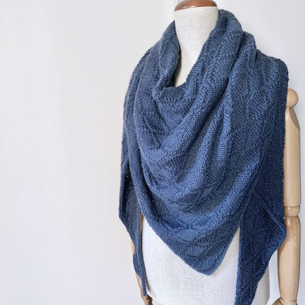 Lake Breeze Shawl by Claudia Eisenkolb knitted using The Fibre Co. Cumbria. | A blue textured shawl draped around a dressform.