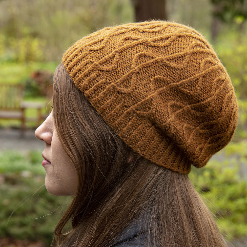 Side profile of Lord's Seat hat. It has wavy cabled ribbing and a slouchy fit.