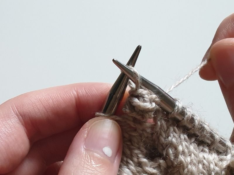 Close up of some hands holding a piece of knitting. A bobble is starting to appear ad some yarn is being wrapped around the base of it.