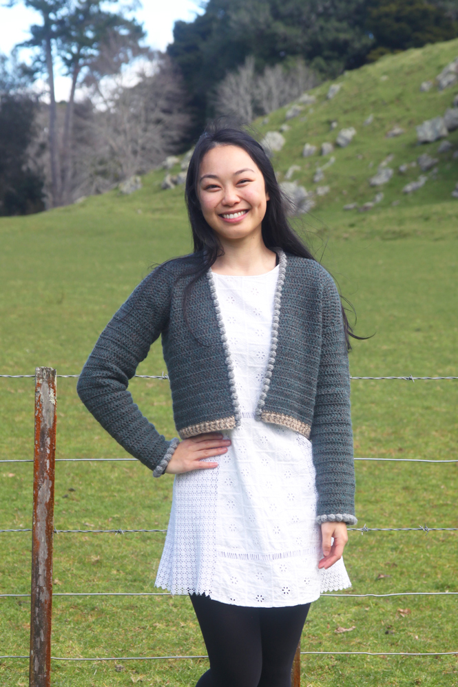 Woman wearing Countryside Cardigan by Grace aka forthefrills over a white tunic in a rural setting | Cropped crochet cardigan pattern