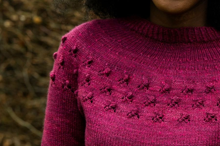 Close up of the Wythop yoke sweater in Acadia. It is knitted in hot pink and has little rosebud bobbles circling the yoke of the sweater. You can see the beautiful multitonal quality of the yarn.