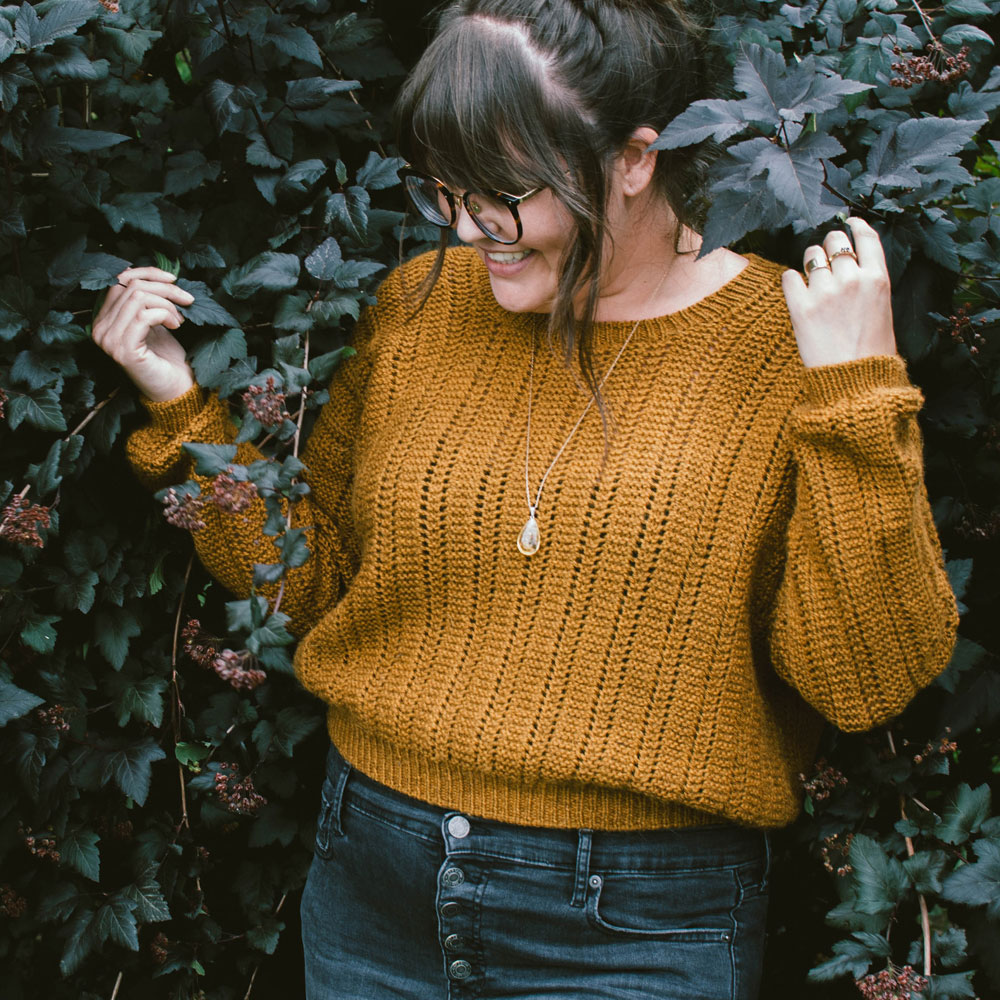 Woman wearing a hand knit textured sweater pictured agains a background of dark leafy foliage | Catbells Sweater Knitting Pattern using The Fibre Co. Cumbria by Megan Nodecker