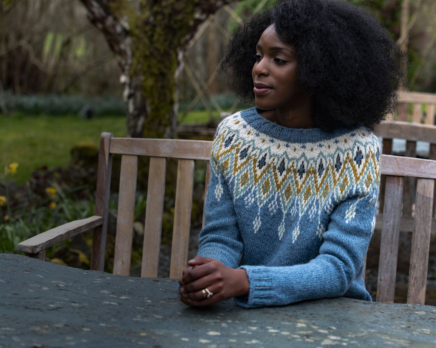 Our model, Joy, is wearing a Seacross colourwork sweater. It is mainly pale blue with pops of cream, yellow, turquoise and brown in the yoke.