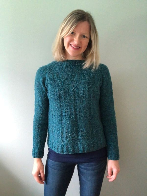 Tammy is wearing a Bowness raglan sweater in teal. It has a grid texture over the body and the yarn looks like tweed.