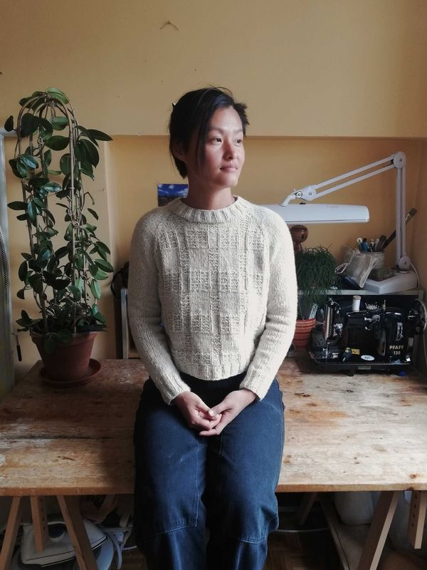 Ting Ting is sat on top of a wooden table wearing jeans and a cream raglan sweater called Bowness. It is cropped with a textured grid stitch across the body.