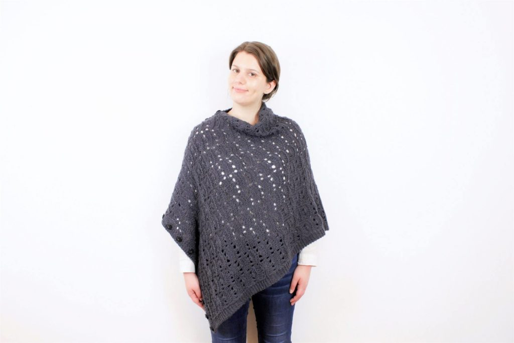 Woman wears the 3-in-accessory as a poncho. Tundra Wrap knitting pattern by Jessica Gore