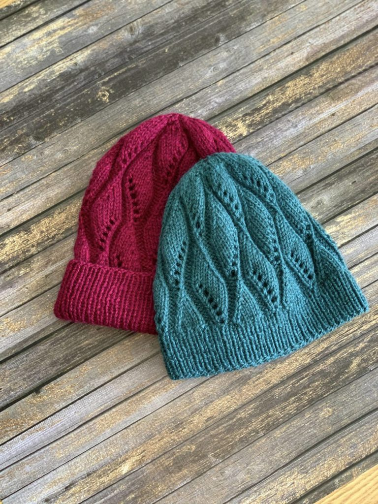 Two hats with a texture design pictured on a wooden table top, one with a folded brim one without. Lydia Hat Knitting Pattern by Crystal Hiatt in The Fibre Co. Cumbria