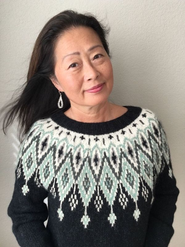 Camay is wearing a colourwork sweater called Seacross. It is mainly black with a cream, turquoise and grey yoke.