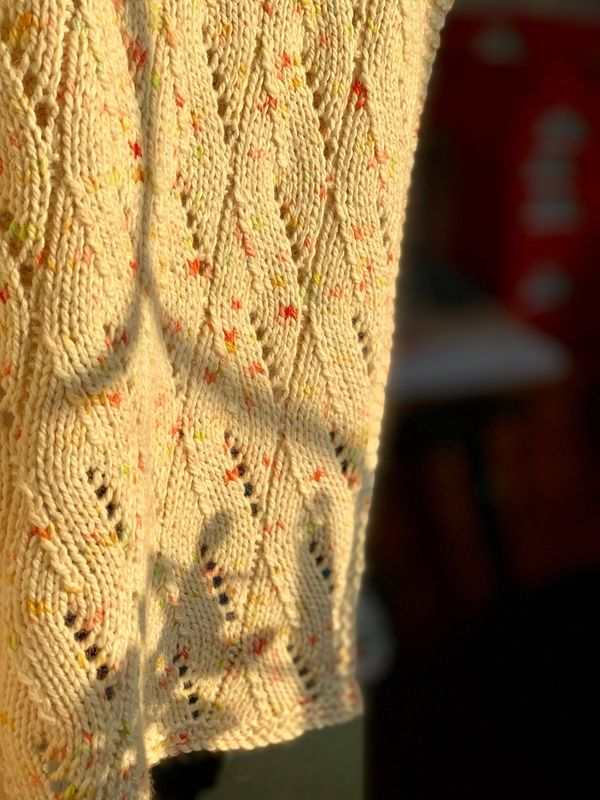 Close up of some beautiful golden sunshine on the Silver Meadows blanket. It is knitted in the speckled Krill colourway which is cream with yellow pink and orange speckles.
