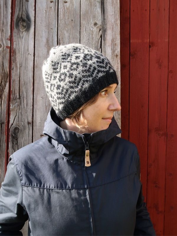 Terhi is standing in front of a wooden door wearing the Tenterhill colourwork hat in grey and black