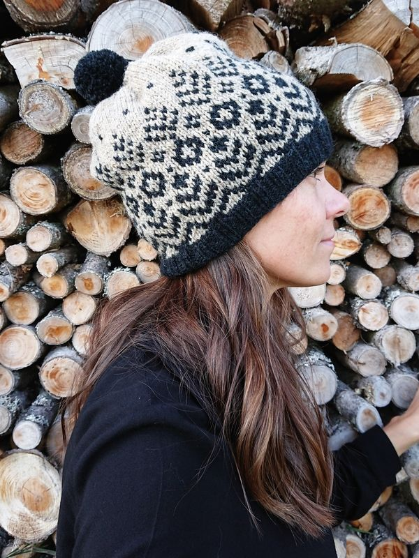 Therese is wearing the Tenterhill colourwork hat in black and beige. It has a black pom pom!