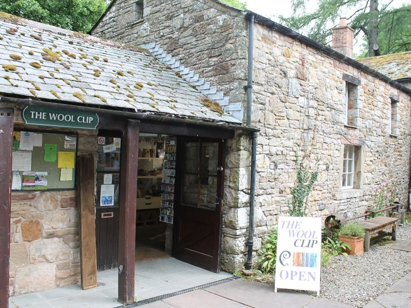 This is the outside of the The Wool Clip. It is an old stone building with a traditional green sign.