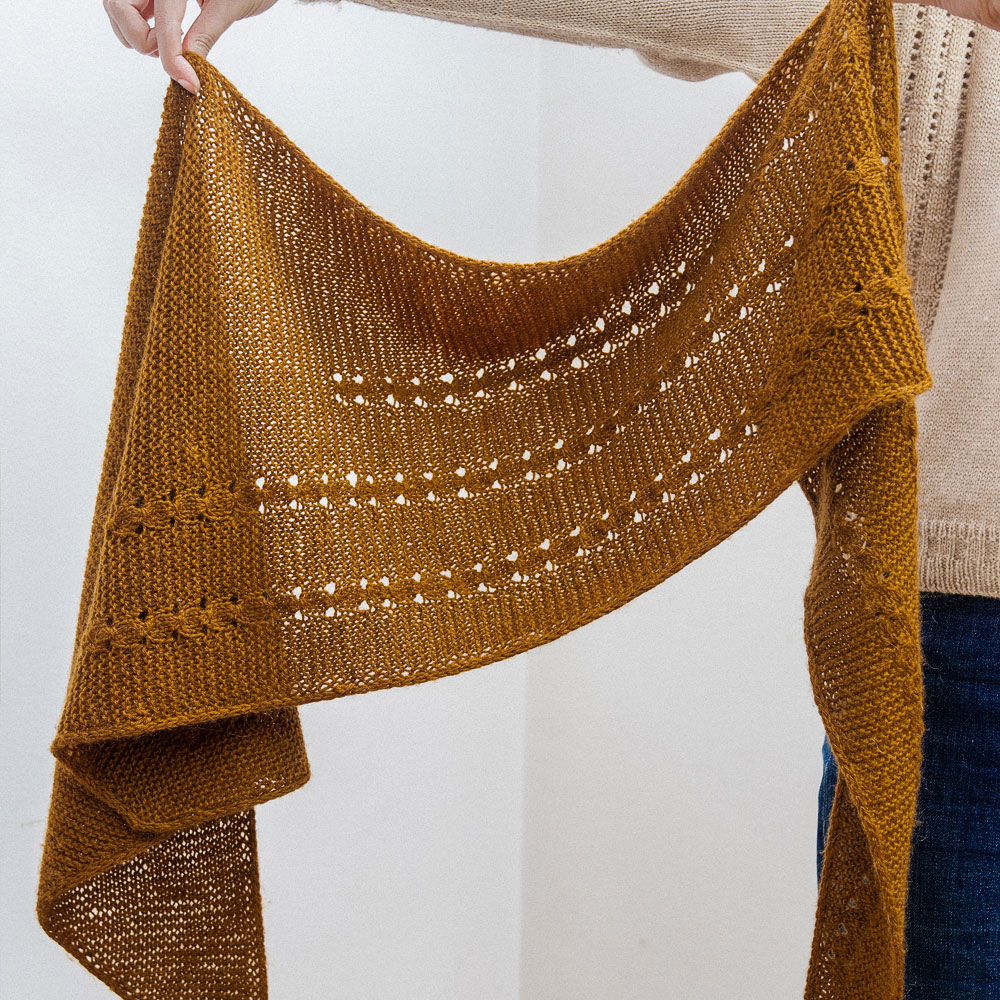 Asymmetric triangle shawl in garter stitch with columns of cluster stitches