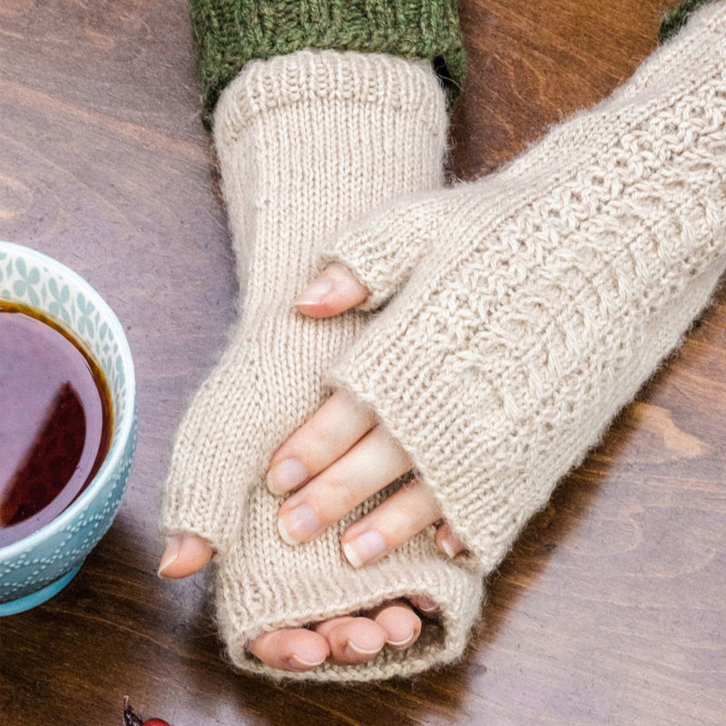 Fingerless mitts in soft beige. They are long and have a simple cable motif over the top of the hand and wrist.